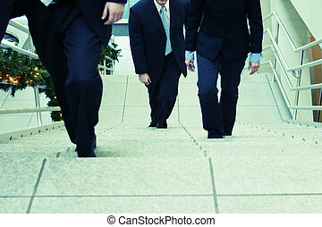 business team - three business people walking up steps