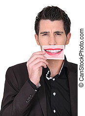 dark-haired man holding picture of female mouth smiling