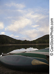 Canoes in a Row - Several green canoes sit in a row along...
