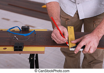 Man marking-off laminate flooring