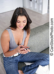 Woman with a cellphone on the sofa