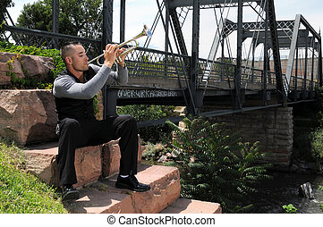 Trumpet player - a musician playing a trumpet by a bridge in...
