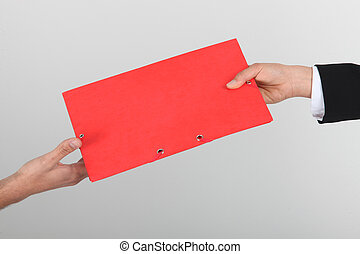 red folder passed from hand to hand