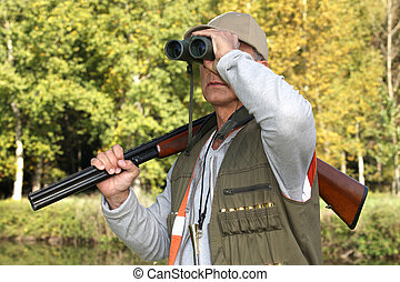 hunter with rifle looking through binoculars