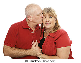 Loving Kisses - Attractive middle-aged couple in love....