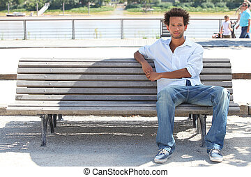 Young man sitting on a public bench