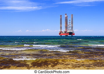 Drilling platform in the sea against a blue sky