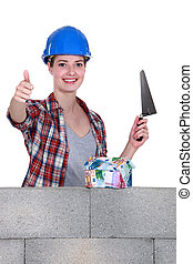 portrait of high-spirited female bricklayer thumb up