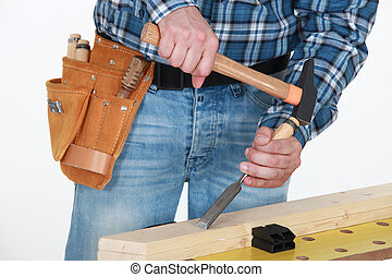 Tradesman chiseling a plank of wood