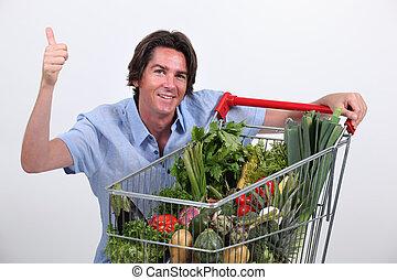 Man kneeling by trolley full of vegetables