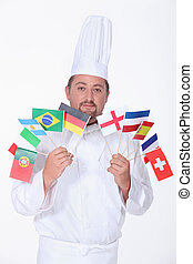 A chef holding a bunch of flags