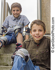 two smiling teenage boys in roller-blading protection kits