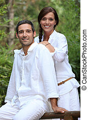 Smiling couple wearing white in a garden