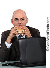 businessman eating a hamburger