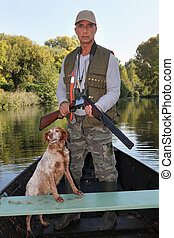 Hunter with dog on boat