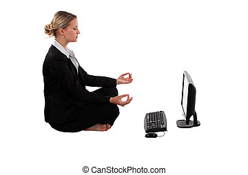 businesswoman meditating in front of her laptop
