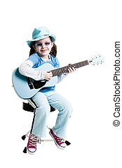 Young girl playing on a guitar while sitting on a white...
