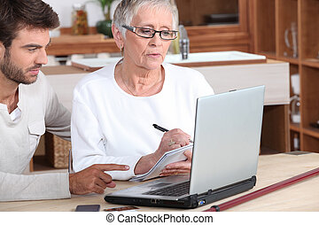 man and senior woman in front of laptop computer