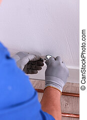 Plumber fixing copper pipe wall