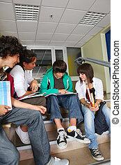 Teenagers sat on school steps