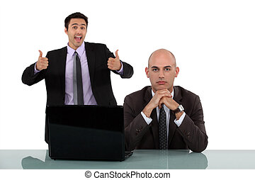Man rejoicing behind his long-faced colleague