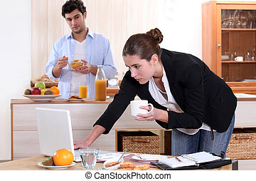 Woman working while eating breakfast
