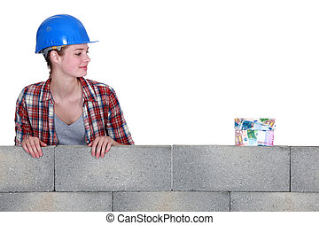 Female builder looking at a house made of money