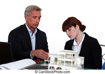 Architects examining a building model