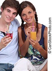 Two teenagers with fruit juice