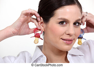 Woman with baby's dummies as earrings