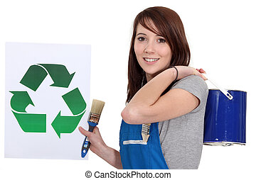 craftswoman painter holding a recycling label