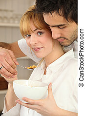 Couple eating bowl of cereal