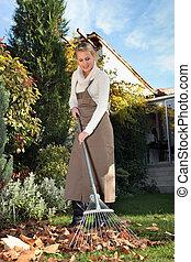 Woman raking leaves in  the garden