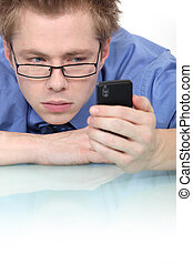 Man staring intently at his mobile phone