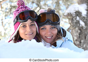 Two young women playing in the snow