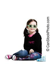 Young girl wearing sun glasses sitting on a blue blanket on...