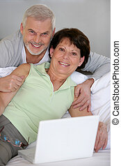 Senior couple on the sofa with a computer