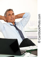50-55 years old man dressed in shirt and tie is relaxing in...