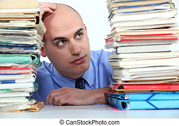 Office worker looking at stacks of files
