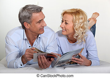 Married couple reading magazine