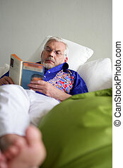 Elderly man reading in bed
