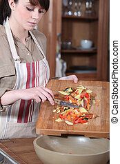 Young woman collecting vegetables peelings