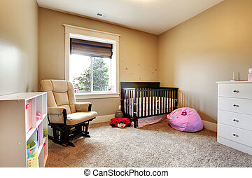 Nursing room for baby girl with brown wood crib. - Nursing...