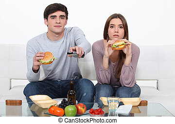 portrait of young couple eating burgers while watching TV