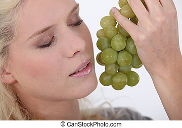 Woman holding a bunch of grapes next to her face