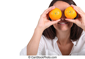 Woman using oranges for eyes