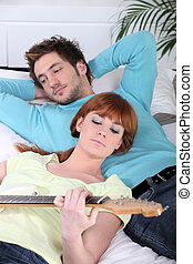 Woman playing the guitar for her boyfriend
