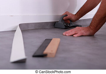 Man trimming linoleum against a skirting board