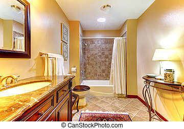 Golden nice bathroom with brown tiles and wood cabinet.