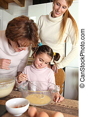 Little girl baking with her mother and grandma